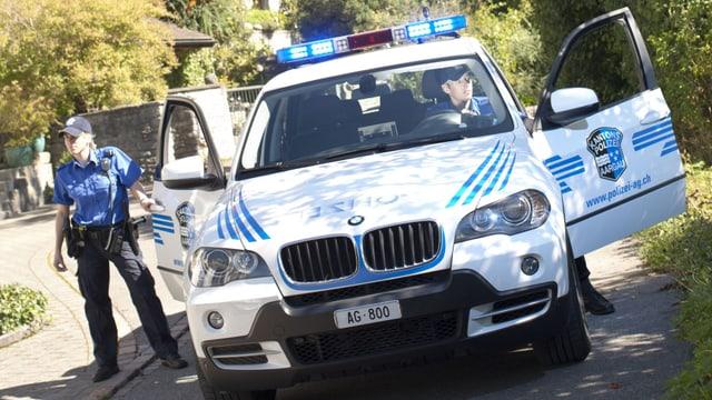 Eine Polizeipatrouille mit zwei Polizisten und einem Streifenwagen im Einsatz.