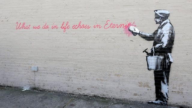 Gesprayter Mann putzt selber weg, was auf die Wand gesprayt ist: «What we do in life echoes in eternity.»