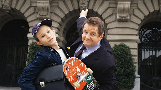 Ein Junge und ein Mann posieren mit Skateboard vor dem Bundeshaus.