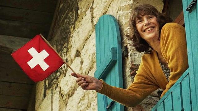 Ein Frau schaut aus einem Fenster und winkt mit einer Schweizerfahne.