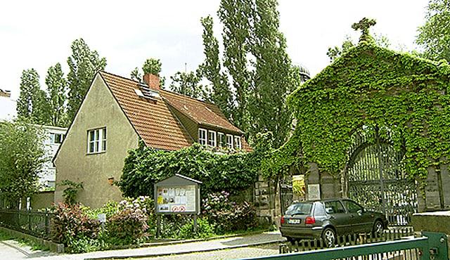 Eingangstor zum Friedhof und kleines Haus daneben