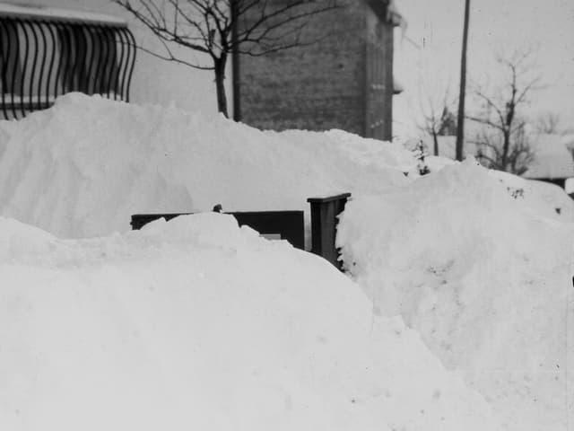 Hohe Schneemauern bei einem Hauseingang.