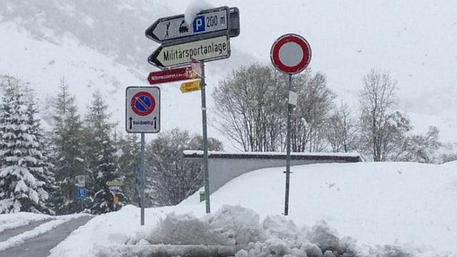 Die schneebedeckte Strasse mit einem Verkehrsschild.