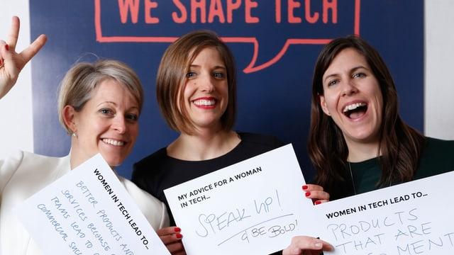 Die drei Frauen lachen in die Kamera und halten Zettel hoch mit ihren Tipps an andere Frauen in der Tech-Branche.