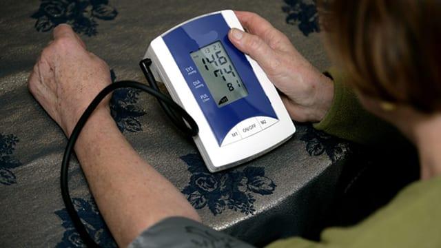 Frau misst sich den Blutdruck