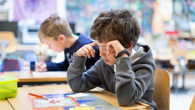 Ein Kind sitzt in einem Schulzimmer und schaut auf ein Schulbuch.