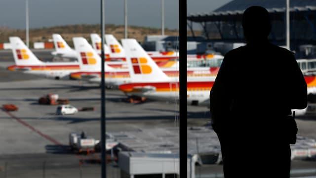 Ein Mann in einem Flughafen schaut sich Flugzeuge der Iberia an.