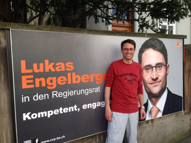 Lukas Engelberger im Joggingdress vor eigenem Wahlplakat