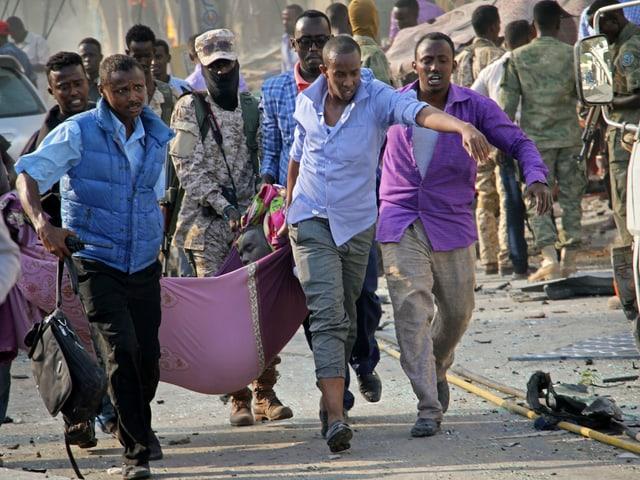 Zivilisten tragen Person in Bahre ab.
