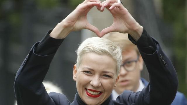 Frau zeigt mit Händen Herzform