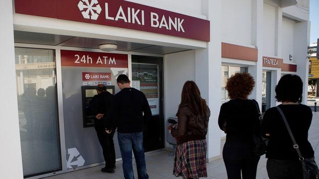 Menschen stehen Schlange vor einem Bankautomaten.