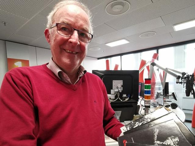 Ein älterer Mann mit Brille und rotem Pullover.