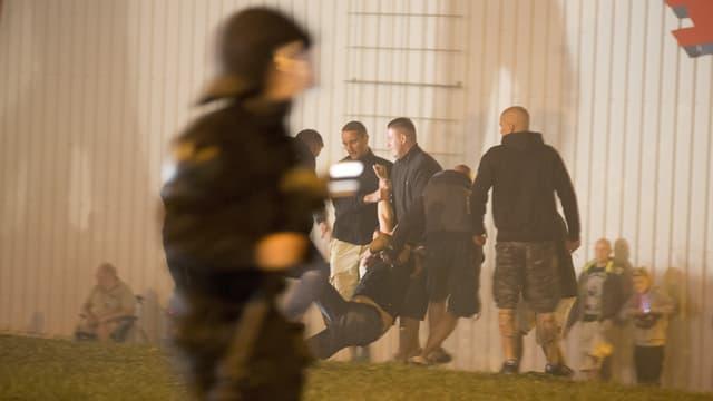 Ein Polizist, dahinter tragen Neo-Nazis einen verletzten Mitstreiter.