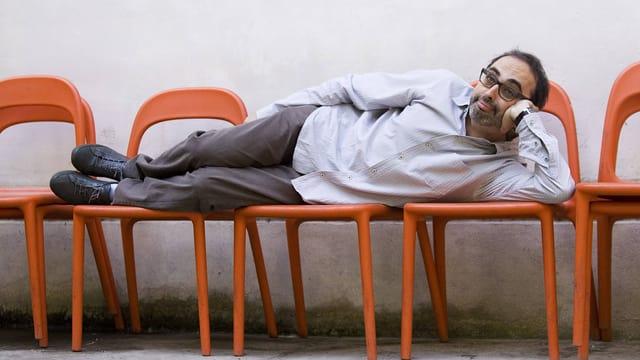 Ein Mann mit Brille liegt auf drei aneinandergereihten, orangen Stühlen und stützt seinen Kopf ab.