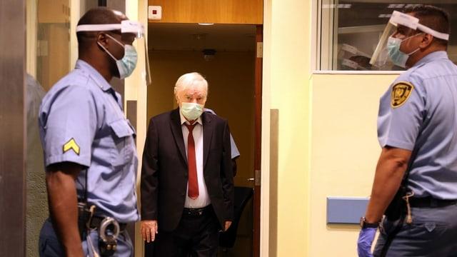 Mladic läuft in Anzug und mit Hygienemaske in den Gerichtssaal, links und rechts sind zwei Polizisten zu sehen.