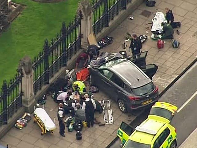 Ein beschädigtes Auto steht auf einem Trottoir, rundherum stehen und knien Rettungskräfte