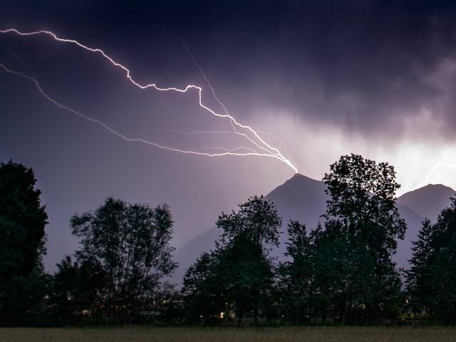 Ein Blitz schlägt in einen Berg ein.