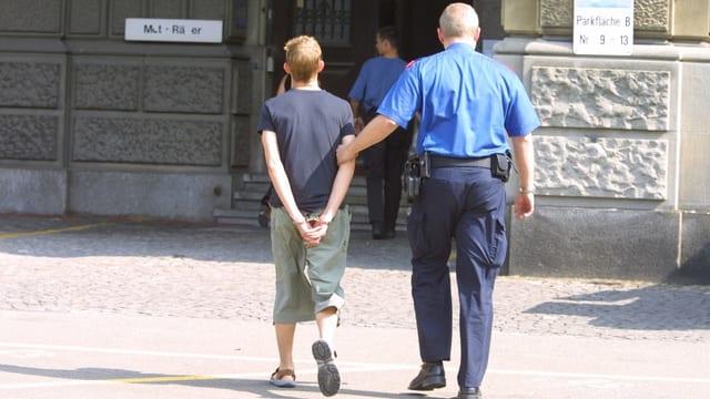 Ein Polizist führt einen Jugendlichen in Handschellen ab (Foto von hinten aufgenommen).