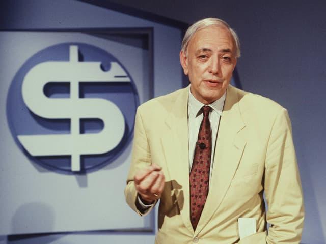 Seriöser, älterer Fernsehmoderator vor einem stilisierten Aeskulap-Stab