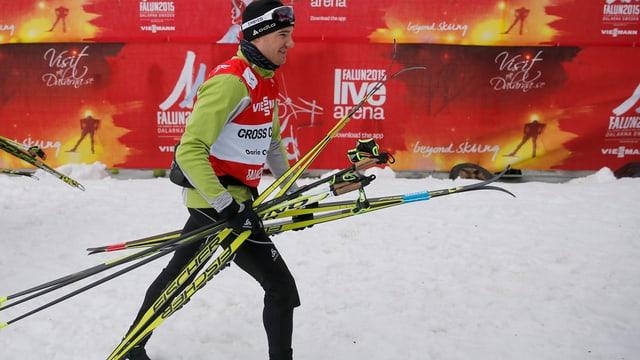 Dario Cologna che porta ses skis da passlung.