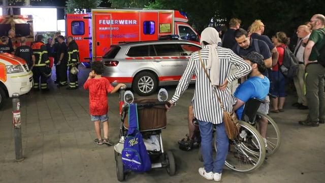 Leute stehen herum. Ein Feuerwehrwagen.