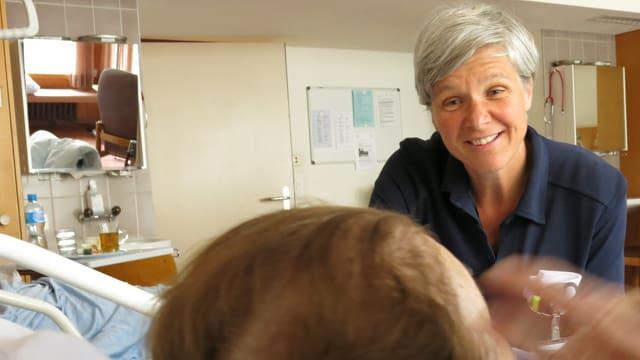 Marlis Stähli sitzt am Bett und spricht mit einer Patientin.