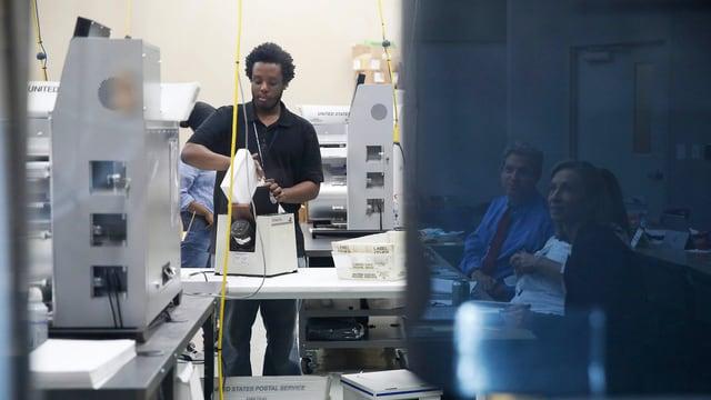 Mann sortiert Stimmzettel in Maschine ein