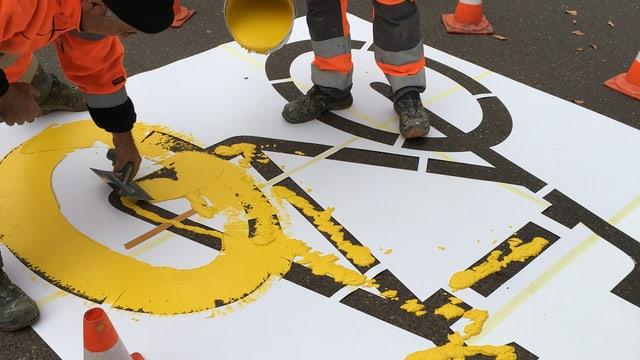 Bauarbeiter bemalen eine Strasse mit einem gelben Velo.