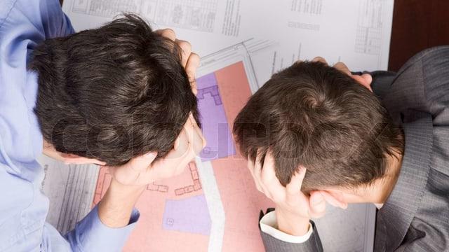 Das Bild zeigt zwei Männer, die sich an den Kopf greifen.