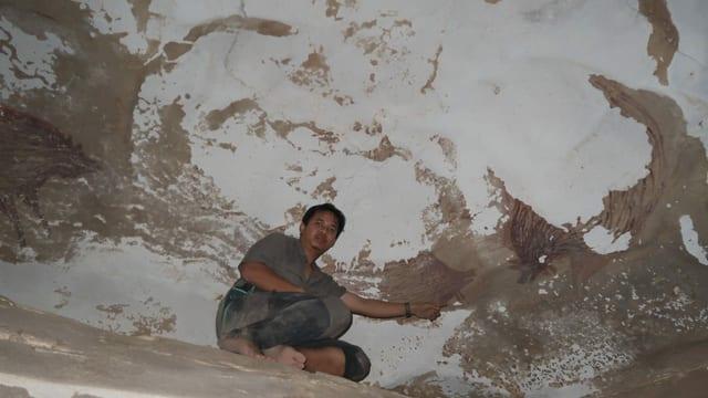 Mann kniet in einer Höhle neben einer Malerei