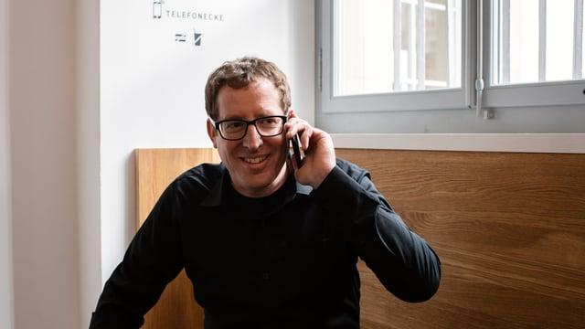 Ein Mann sitzt auf einer Bank und telefoniert mit seinem Smartphone.