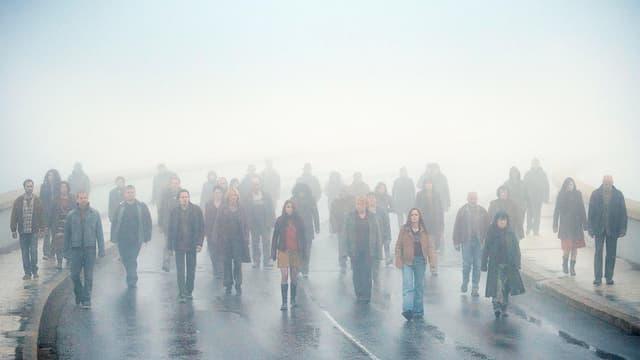 Eine Menschenmasse läuft im Nebel mitten auf einer Strasse.