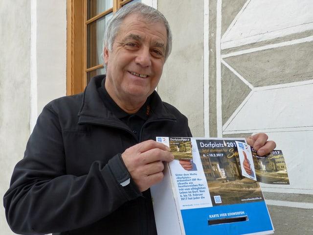 Ein Mann zeigt einen selbst gebastelten Briefkasten aus Karton.