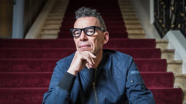 Autor Tom Kummer sitzt in Denkerpose auf einer Hoteltreppe.