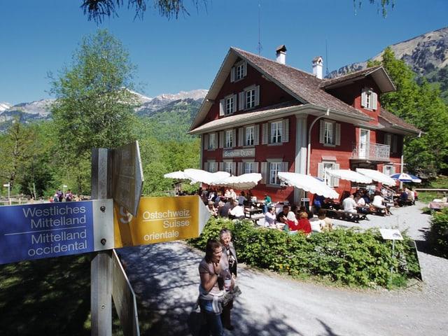 Restaurant mit Sonnenschirmen in der Mitte des Freilichtmuseums. Davor ein Wegweiser.