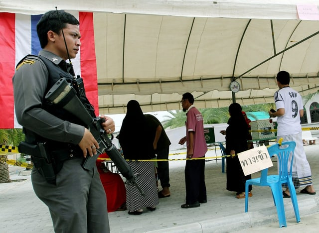 Bürger bei einer Wahl, im Vordergrund ein Mann mit Sturmgewehr