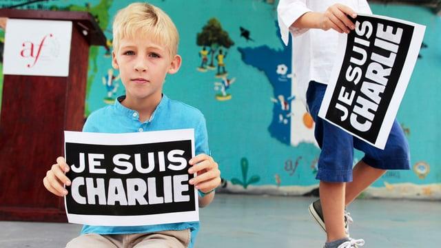 Ein blonder Junge hält ein Schild «Je suis Charlie».