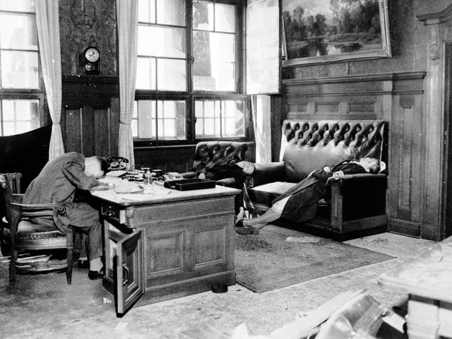 Ein Mann liegt mit dem Kopf auf einem Pult. Er ist tot. Eine Frau liegt tot auf einem Sofa, eine weitere im Sessel.