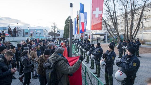 Pegida demonstriert: Man sieht einige Demonstranten, die Polizisten gegenüber stehen. Man sieht Fahnen von der Schweiz, Frankreich und Deutschland.