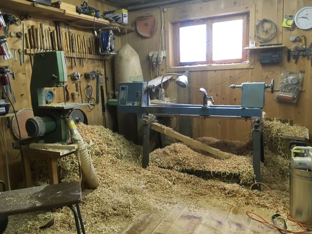 Holzwerkstatt mit viel Sägespänen auf dem Boden.