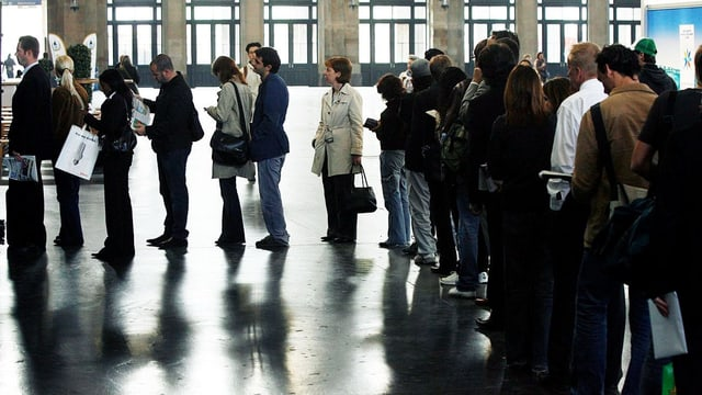 Leute stehen im Haupbahnhof Zürich ab.