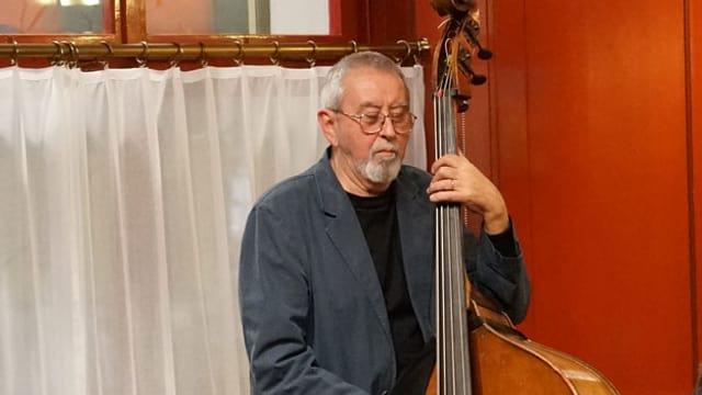 Isla Eckinger am Kontrabass spielend, vor einem weissen Vorhang stehend.