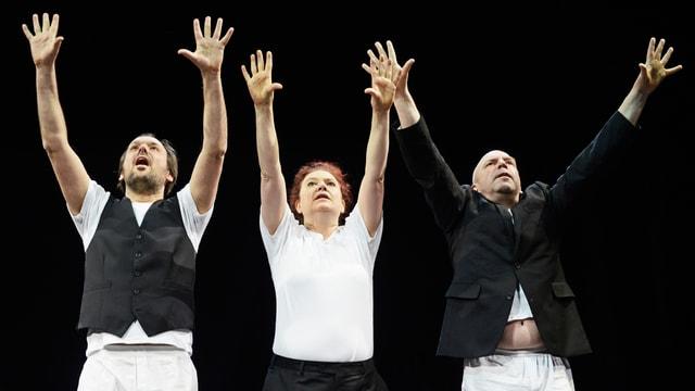 Bühnenbild: Zwei Männer und eine Frau strecken sich zum Himmel.