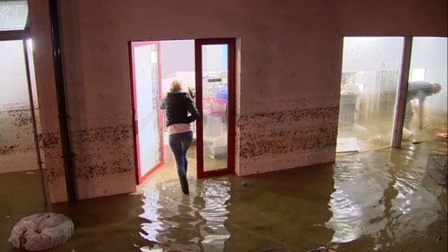Eine Frau betritt einen Laden, der überschwemmt ist