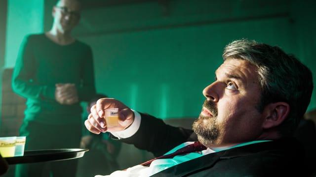 Luc Conrad trinkt einen kleinen Becher mit einer Flüssigkeit.