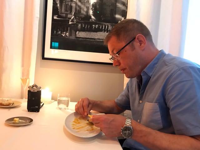 Mann sitzt vor fast leeren Teller und isst noch den Rest