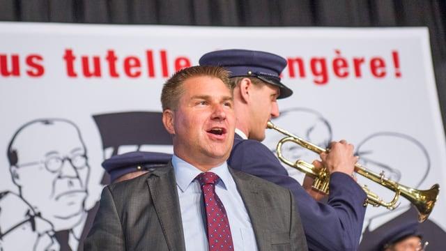 Toni Brunner vor einem Plakat und einen Trompetenspieler.