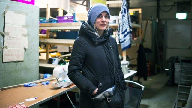 Eine junge Frau steht warm eingepackt in einer Lagerhalle.