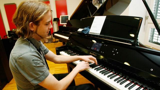 Ein Mann sitzt an einem E-Klavier und spielt.