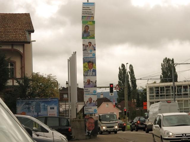 Sieben Plakate an einer Lichtsäule.